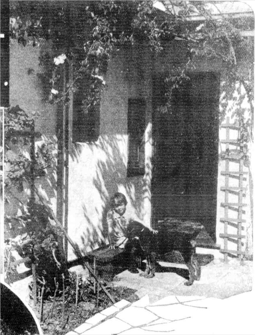 Jacqueline Jackson with Dusty at the rose-hung doorway of the lovely home  of Mr. and Mrs. James R. Jackson, on a Seaforth cliff above The Spit. cec069b394c5